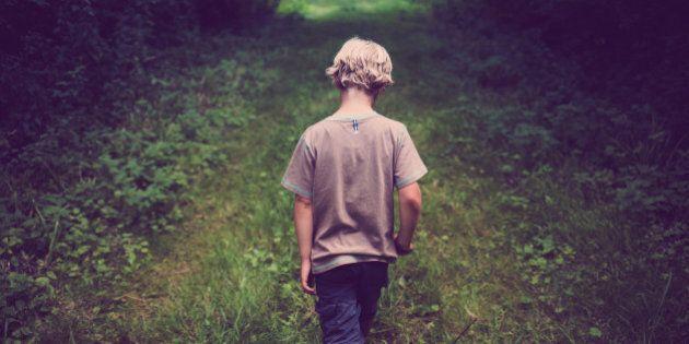 7 year old boy walks down path through