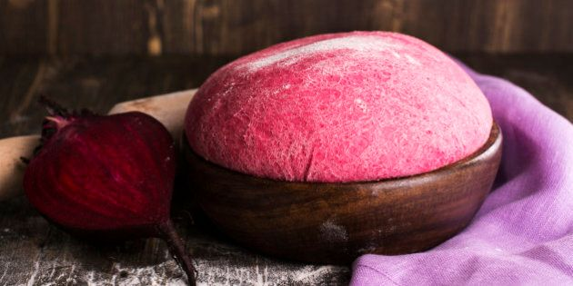 Pink beet dough and ingredients over wooden table. Selective focus. Vintage style