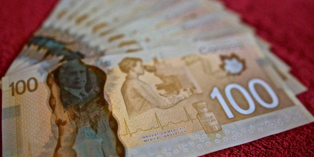Canadian 100 dollar bills, $100.00,fanned out on red background