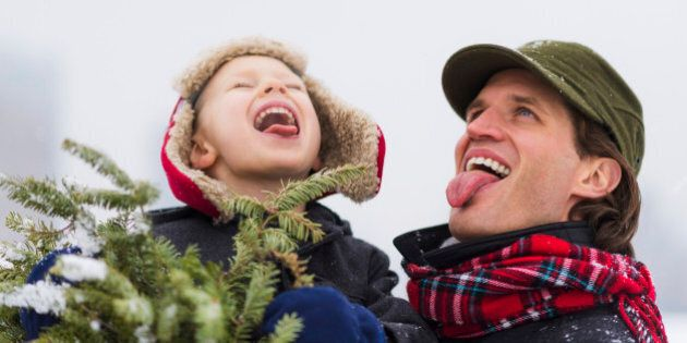 Father and son (6-7) catching snowflakes on tongue, Jersey City, New Jersey, USA