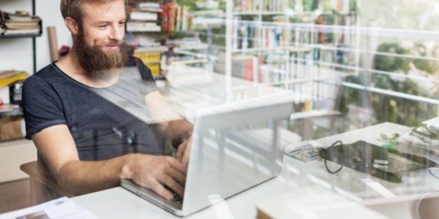 Young bearded man sitting on desk in his home office and working on