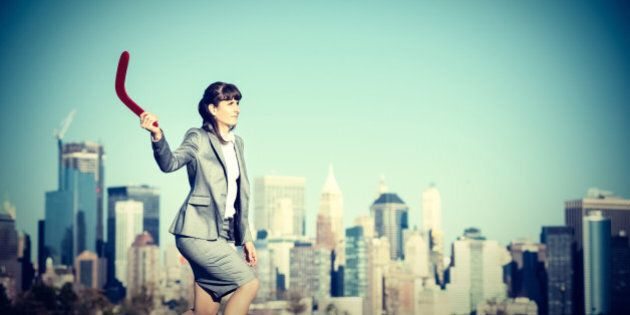 Businesswoman throwing a Boomerang. Investment and gain concept.