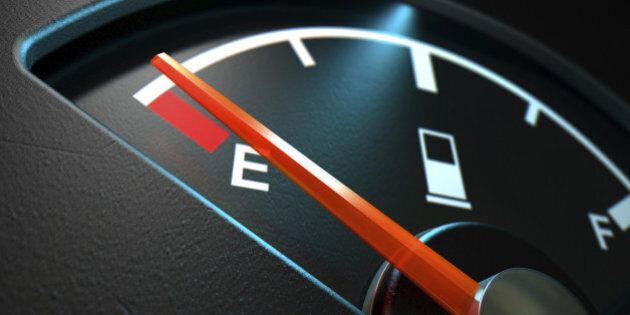 A closeup of a backlit illuminated gas gage with the needle indicating an empty tank on an isolated dark