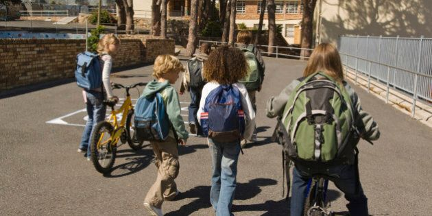 Children walking with bicycles and backpacks