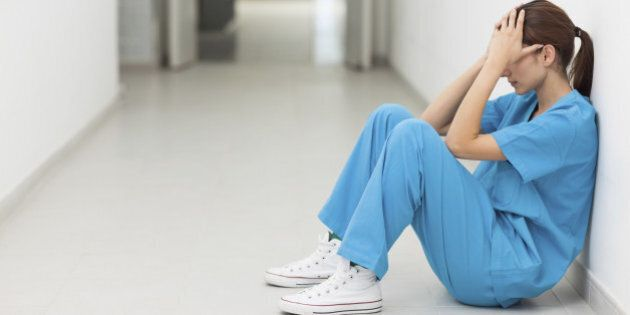Nurse sitting in a corridor while holding her head in a