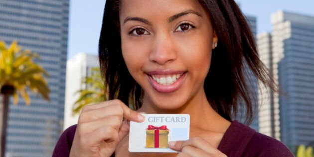 Woman smiling holding a gift card
