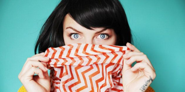 Woman holding bright scarf over lips with shocked