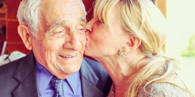 Woman kisses an older man on the cheek