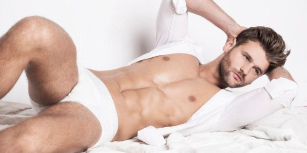 Handsome man waking up in the morning in white linen and underwear