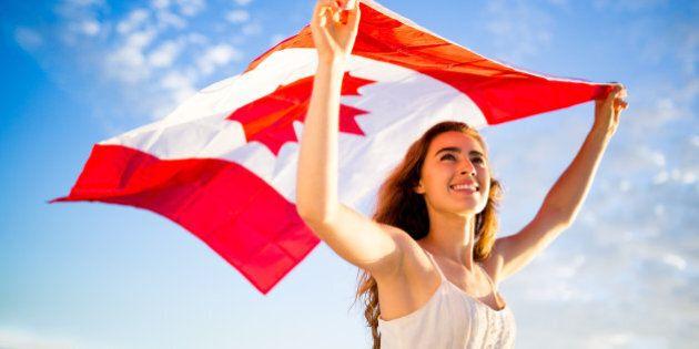 Woman holding canadian flag against blue sky