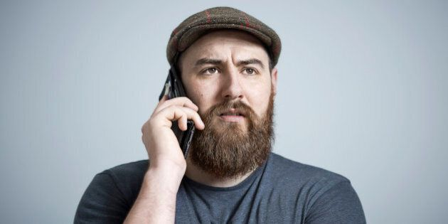 Portrait of bearded male wearing brown cap, making a phone call on smart phone