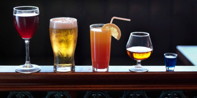 Standing on a banister, an assortment of various sizes and shapes of alcoholic drinks, ranging from shot, brandy, cocktail, beer and wine