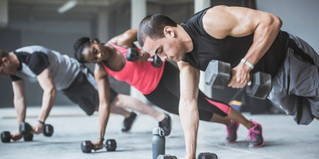 Athletes doing push-ups with dumbbells on