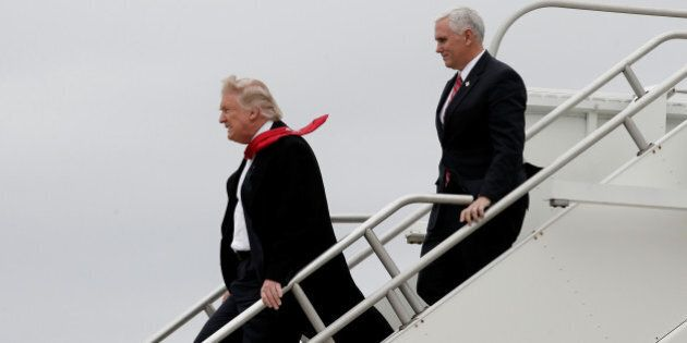 U.S. President-elect Donald Trump and Vice-President elect Mike Pence walk off Trump's plane upon their...