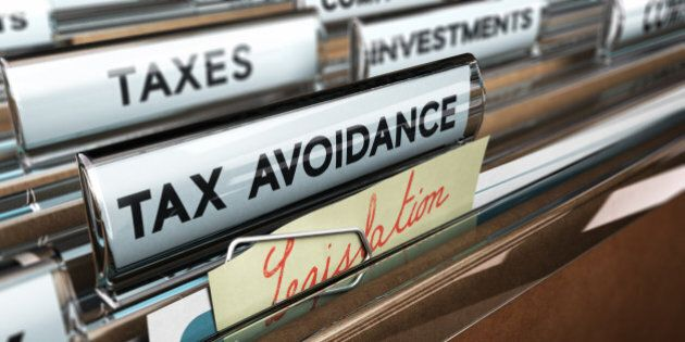Close up on a file tab with the text tax avoidance, focus on a yellow, note where it is hanwritten legislation,...