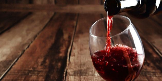Red wine is poured from bottle to glass, wooden