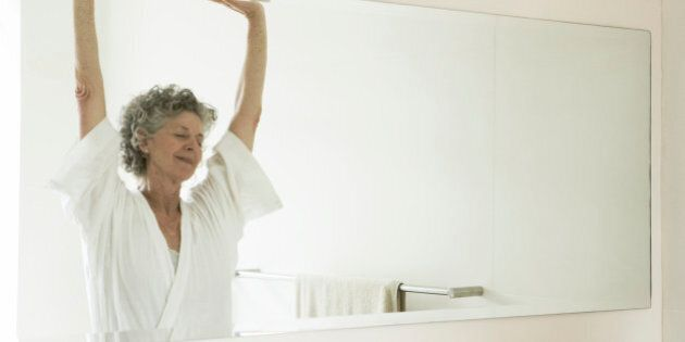 Mature 65 year old woman stretching out in bathroom
