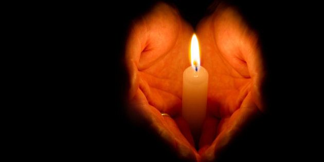 Religious concept. Man hands holding a burning candle on dark
