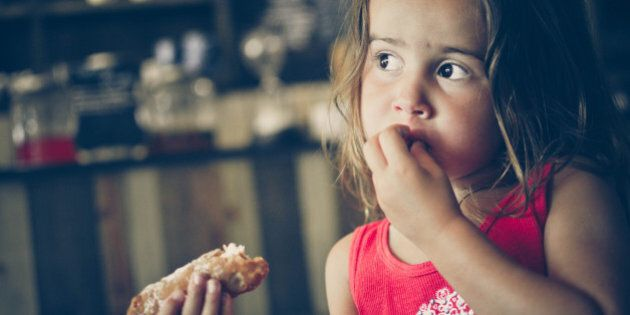 Young girl eating a cannoli in a cafe