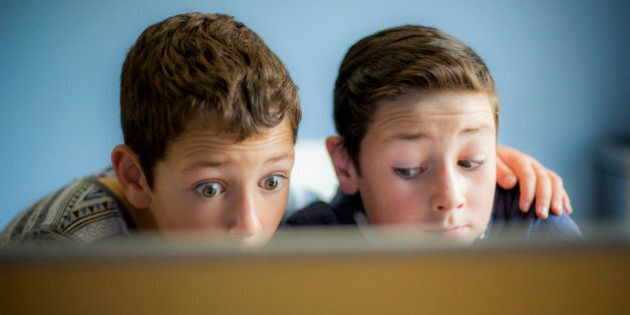 Two surprised boys using a laptop