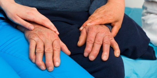 Caring hands of a nurse and doctor for elderly patient with Parkinson's