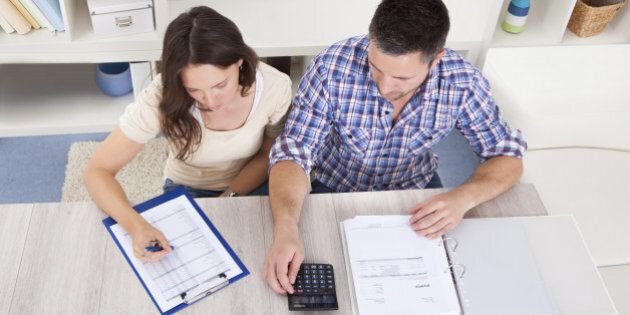 Portrait Of A Young Couple Calculating Finance At