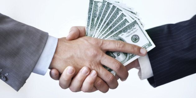 Studio shot of two men shaking hands after making a monetary