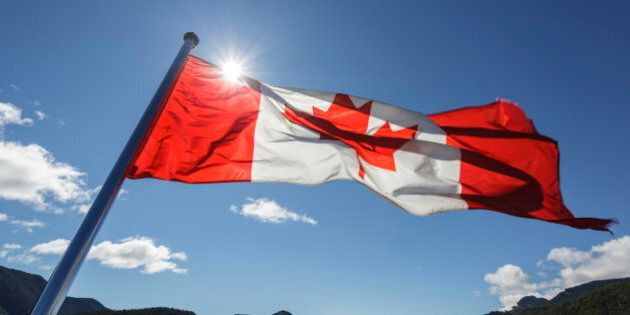 The Canadian Flag flies from the stern of the Uchuck 111 as it traverses Esperanza Inlet, British Columbia,