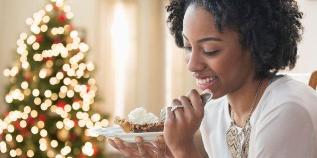 Mixed race woman eating dessert by Christmas