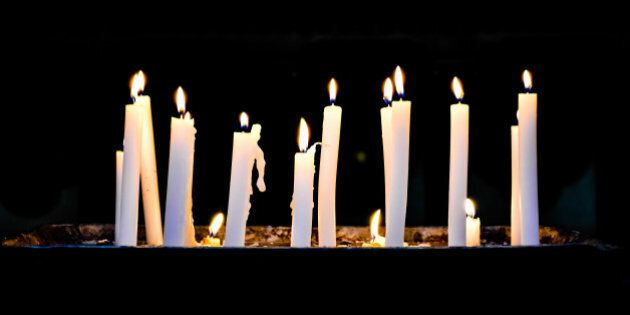 Several candlelights lit up in a row against black background