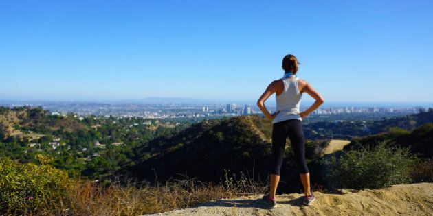Beautiful Woman overlooking Los Angeles from a local hiking trail in Franklin Canyon, Beverly Hills, California