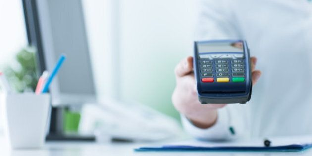 Female pharmacist holding a payment terminal, medical care cost concept
