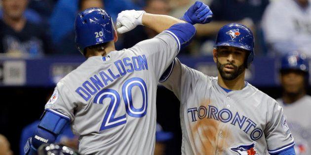 Toronto Blue Jays' Josh Donaldson (20) celebrates with on-deck batter Jose Bautista after hitting a home...