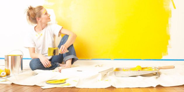 Young woman sitting on the floor , holding a paintbrush