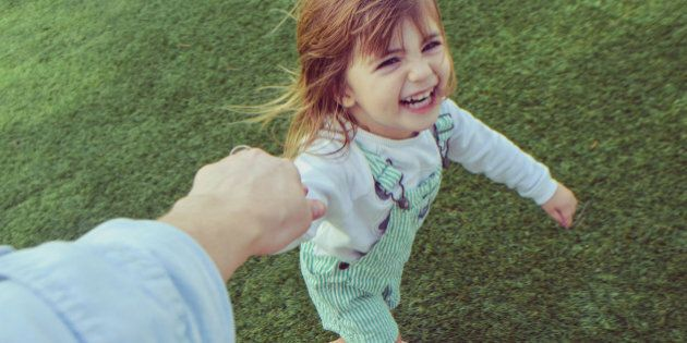 Silly little girl holding a parents hand barefoot in the grass,