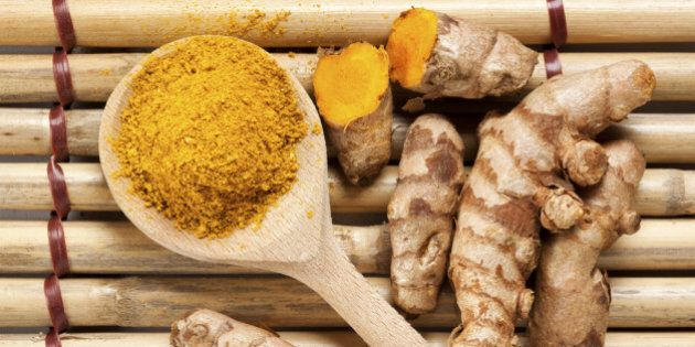 Ground turmeric on wooden spoon and rhizomes on bamboo mat, from above