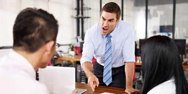 bad-tempered caucasian business executive yelling at two asian subordinates in