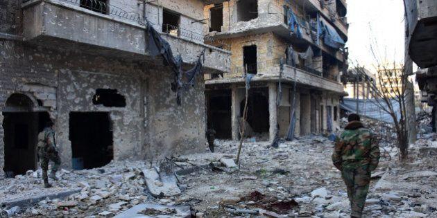 Syrian pro-government forces walk amidst heavy destruction in Aleppo's Bustan al-Basha neighbourhood...