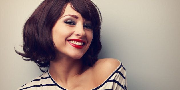 Happy laughing young woman with short hair in fashion blouse. Vintage closeup
