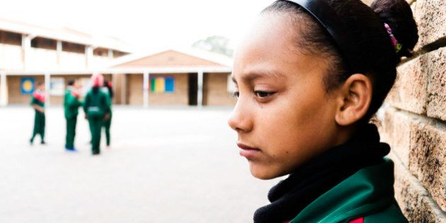 A sad school girl leans against the wall of a school courtyard. Other children play in the background.