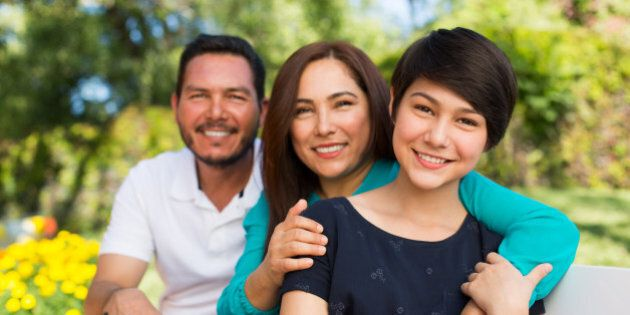 Portrait of happy family smiling together in a park