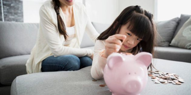 Mother watching daughter deposit coin into piggy