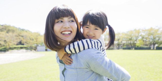 Close-up Of A Mother Giving Piggyback Ride To Her Smiling Daughter