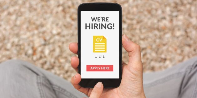 Hands holding smartphone with we are hiring apply now concept on screen. All screen content is designed...