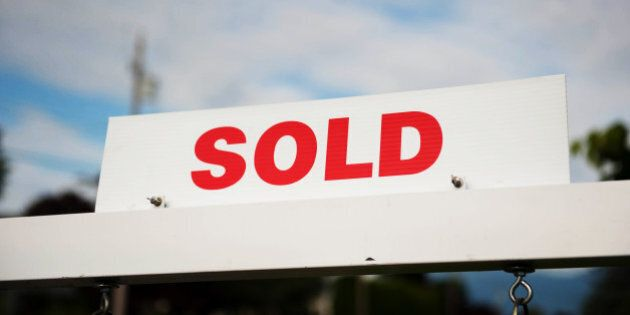 Real estate sold sign against a slightly cloudy blue sky.
