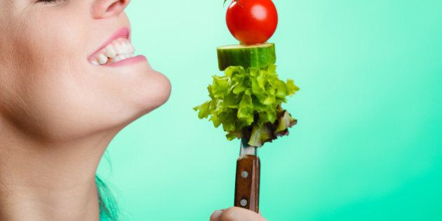 Healthy eating and diet concept. Closeup happy young woman holding vegetables on green blue background....