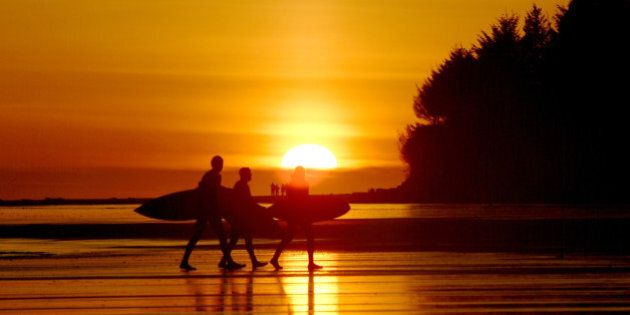 '3 surfers walking with surfboards at sunset on a beach in Tofino, BC, Canada. Camera: Fuji