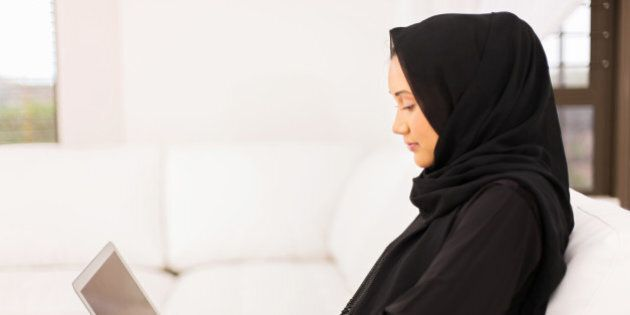 pretty young middle eastern woman using laptop at