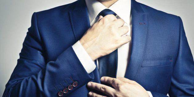 Businessman in blue suit adjusting his tie