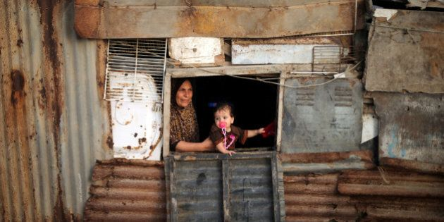 A Palestinian woman and her child look out of the window of their shelter in Deir al-Balah refugee camp...